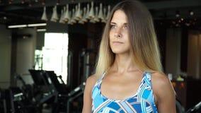Ελκυστικό κορίτσι που τρέχει treadmill στη γυμναστική Πλήρες πορτρέτο προσώπου φιλμ μικρού μήκους
