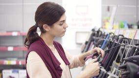 Ελκυστικό κορίτσι σε 20 της ` s που επιλέγουν τον επίπεδο σίδηρο από μια ποικιλία στο κατάστημα συσκευών Περπάτημα στο τμήμα οικο φιλμ μικρού μήκους