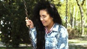 Ελκυστικό κορίτσι στην ταλάντευση σακακιών τζιν στην ταλάντευση στο πάρκο απόθεμα βίντεο