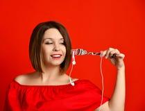 Ελκυστικό κορίτσι στο κόκκινο φόρεμα που κρατά ένα δίκρανο στα χέρια στο βούλωμα ακουστικών Προετοιμάστηκε να φάει στοκ φωτογραφία