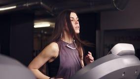 Ελκυστικό κορίτσι brunette με μακρυμάλλη σε 20 της ` s που φορούν dryfit sportswear, που τρέχει treadmill απόθεμα βίντεο