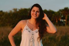 Ελκυστικό μακροχρόνιο σγουρό μαλλιαρό θηλυκό πρότυπο Brunette που θέτει και που χαμογελά για τη κάμερα έξω Στοκ φωτογραφίες με δικαίωμα ελεύθερης χρήσης