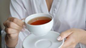 Ελκυστικό μαύρο τσάι ποτών γυναικών από τη μικρή συνεδρίαση φλυτζανιών στην καρέκλα απόθεμα βίντεο