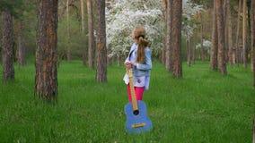 Ελκυστικό μικρό κορίτσι που στέκεται την άνοιξη το πάρκο με μια κιθάρα, μια όμορφους πράσινους χλόη τοπίων και κορμούς των κωνοφό απόθεμα βίντεο