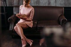 ελκυστικό νέο βιβλίο ανάγνωσης γυναικών στον καναπέ Στοκ Φωτογραφία
