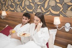 Ελκυστικό νέο ζεύγος στις άσπρες τηβέννους, που απολαμβάνει τα τρόφιμα και το ποτό στοκ εικόνες