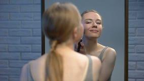 Ελκυστικό νέο θηλυκό ισχύον μέτωπο σκονών προσώπου του καθρέφτη, που χαμογελά στη κάμερα απόθεμα βίντεο