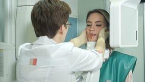 Ελκυστικό νέο κορίτσι που κάνει την εξέταση των δοντιών με τη χρησιμοποίηση του πανοραμικού και cephalometric ανιχνευτή ακτίνας X απόθεμα βίντεο