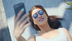 Ελκυστικό νέο κορίτσι που κάνει selfie και που βρίσκεται στο πάρκο φιλμ μικρού μήκους