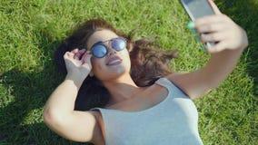Ελκυστικό νέο κορίτσι που κάνει selfie στη χλόη στο πάρκο απόθεμα βίντεο