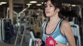 Ελκυστικό νέο κορίτσι που τρέχει treadmill καρδιο ασκήσεις στη γυμναστική απόθεμα βίντεο