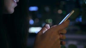 Ελκυστικό νέο κορίτσι που χρησιμοποιεί Smartphone με το θολωμένο μπλε Bokeh υπόβαθρο φω'των νύχτας οδών αστικό 4K Μπανγκόκ απόθεμα βίντεο