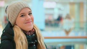 Ελκυστικό νέο κορίτσι στο χειμερινό καπέλο που εξετάζει τη κάμερα και το χαμόγελο αγορές κεντρικών εσωτερικές λεωφόρων απόθεμα βίντεο