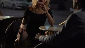 Ελκυστικό ξανθό θηλυκό παραπλανώντας άτομο στο πεζούλι εστιατορίων, υπηρεσία συνοδειών απόθεμα βίντεο