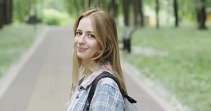Ελκυστικό ξανθό κορίτσι που περπατά στο πάρκο φιλμ μικρού μήκους