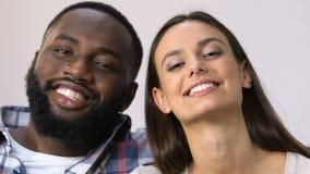 Ελκυστικό οικογενειακό ζεύγος αναμιγνύω-φυλών που χαμογελά ειλικρινά στη κάμερα, σχέσεις απόθεμα βίντεο