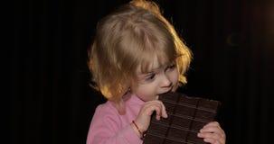 Ελκυστικό παιδί που τρώει έναν τεράστιο φραγμό της σοκολάτας ξανθό χαριτωμένο κορίτσι απόθεμα βίντεο