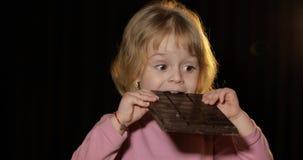 Ελκυστικό παιδί που τρώει έναν τεράστιο φραγμό της σοκολάτας Χαριτωμένο ξανθό κορίτσι στοκ εικόνα με δικαίωμα ελεύθερης χρήσης