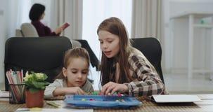 Ελκυστικό παιχνίδι αδελφών δύο κοριτσιών μαζί στον πίνακα κουζινών ενώ η γιαγιά τους που διαβάζει ένα βιβλίο στον καναπέ επάνω φιλμ μικρού μήκους