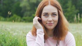 Ελκυστικό όμορφο κοκκινομάλλες πρόσωπο φακίδων πορτρέτου γυναικών υπαίθρια σε αργή κίνηση απόθεμα βίντεο