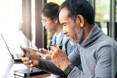 Ελκυστικό ώριμο ασιατικό άτομο με την άσπρη μοντέρνη κοντή γενειάδα hispter που φαίνεται ειδήσεις ανάγνωσης smartphone ή κοινωνικ στοκ φωτογραφίες