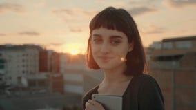 Ελκυστικό brunette με τη συσκευή στη στέγη στο ηλιοβασίλεμα απόθεμα βίντεο