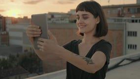 Ελκυστικό brunette με τη συσκευή στη στέγη στο ηλιοβασίλεμα φιλμ μικρού μήκους