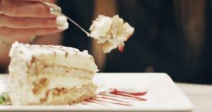 Ελκυστικό brunette που τρώει ένα κομμάτι του κέικ σε έναν καφέ απόθεμα βίντεο