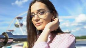 Ελκυστικό brunette στα γυαλιά που θέτουν για τη κάμερα, που εκφράζει την εσωτερική εμπιστοσύνη φιλμ μικρού μήκους