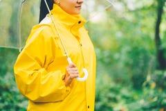 Ελκυστικό unrecognizable νέο κορίτσι στο κίτρινο αδιάβροχο στο πάρκο ή δάσος με τη διαφανή ομπρέλα, ημέρα φθινοπώρου εστίαση στοκ εικόνες