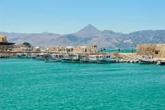 13 07 2014 Ελλάδα, Knososs Ο κόλπος θάλασσας με έναν τοίχο του αρχαίου αναγνωριστικού σήματος Σε μια αποβάθρα πολλά αλιευτικά σκά στοκ εικόνες