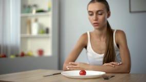 Ελλειπής γυναίκα που εξετάζει τη μικρή μερίδα του γεύματος, εξαντλημένο σώμα, αυστηρές διατροφές στοκ φωτογραφία