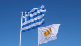 Ελληνικές σημαίες της Κύπρου και που χτυπούν στον αέρα σε έναν πόλο Ελληνικής και της Κύπρου σημαία μπλε ουρανού, φιλμ μικρού μήκους