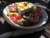 Ελληνική σαλάτα με το τυρί φέτας, τα κόκκινα κρεμμύδια, τις ντομάτες, oregano, το πρόσθετα παρθένο έλαιο και τα καρυκεύματα Στοκ Φωτογραφίες