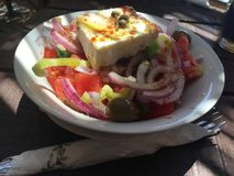 Ελληνική σαλάτα με το τυρί φέτας, τα κόκκινα κρεμμύδια, τις ντομάτες, oregano, το πρόσθετα παρθένο έλαιο και τα καρυκεύματα Στοκ Εικόνα