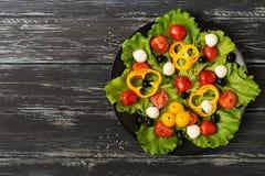 Ελληνική σαλάτα σε ένα μαύρο πιάτο, ξύλινο παλαιό υπόβαθρο Τοπ άποψη με το διάστημα Στοκ Εικόνα