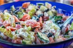 Ελληνική σαλάτα σε ένα μπλε πιάτο, στενή, εκλεκτική εστίαση Στοκ φωτογραφία με δικαίωμα ελεύθερης χρήσης