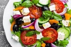 ελληνική σαλάτα Σαλάτα φρέσκων λαχανικών με την ντομάτα, το κρεμμύδι, τα αγγούρια, το βασιλικό, το πιπέρι, τις ελιές, το μαρούλι  Στοκ εικόνα με δικαίωμα ελεύθερης χρήσης