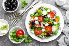 ελληνική σαλάτα Σαλάτα φρέσκων λαχανικών με την ντομάτα, το κρεμμύδι, τα αγγούρια, το βασιλικό, το πιπέρι, τις ελιές, το μαρούλι  Στοκ φωτογραφίες με δικαίωμα ελεύθερης χρήσης