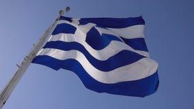 Ελληνική σημαία που κυματίζει ενάντια στο μπλε ουρανό απόθεμα βίντεο