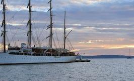 Ελλιμενισμένο παλαιό πλέοντας σκάφος που δένεται σε μια αποβάθρα στο ηλιοβασίλεμα Στοκ Εικόνες