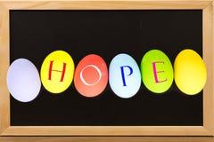 ΕΛΠΙΔΑ στα αυγά ζωηρόχρωμα στον πίνακα κιμωλίας με το διάστημα αντιγράφων στοκ φωτογραφία με δικαίωμα ελεύθερης χρήσης