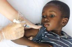 Εμβολιασμός για τα αφρικανικά παιδιά: λίγο μαύρο αγόρι που παίρνει μια έγχυση από μια νοσοκόμα στοκ εικόνες