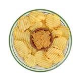 Εμβύθιση Hummus σε ένα κύπελλο με τα τσιπ πατατών σε ένα πιάτο Στοκ Εικόνες