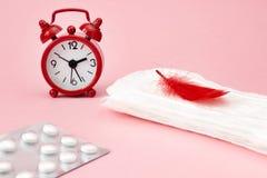 Εμμηνορροϊκά μαξιλάρια, ημερολόγιο περιόδου αίματος, ρολόγια και χάπια Άσπρες φαρμακευτικές ταμπλέτες Προστασία πόνου περιόδου εμ στοκ φωτογραφία