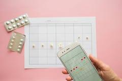 Εμμηνορροϊκός κύκλος Ημερολόγιο για το μήνα με τα σημάδια και μια κινητή εφαρμογή στην οθόνη smartphone στοκ φωτογραφίες