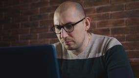 Εμπαθές άτομο με τα γυαλιά που λειτουργούν με το lap-top στο γραφείο Ένας αρσενικός συγγραφέας δακτυλογραφεί το κείμενο στο πληκτ φιλμ μικρού μήκους