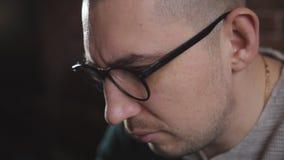 Εμπαθές άτομο με τα γυαλιά που λειτουργούν με το lap-top στο γραφείο Ένας αρσενικός συγγραφέας δακτυλογραφεί το κείμενο στο πληκτ απόθεμα βίντεο
