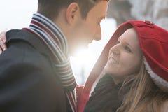 Εμπαθές ερωτευμένο φίλημα ζευγών και αγκάλιασμα μεταξύ αναδρομικά φωτισμένου Στοκ Εικόνες