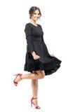 Εμπαθές ισπανικό θηλυκό χορευτών στο μαύρο ρέοντας φόρεμα που χαμογελά και που εξετάζει τη κάμερα Στοκ Εικόνες